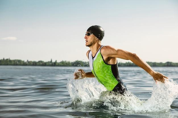 Professioneller triathlet, der im offenen wasser des flusses schwimmt. mann mit schwimmausrüstung, der am sommertag triathlon am strand praktiziert. konzept des gesunden lebensstils, des sports, der aktion, der bewegung und der bewegung.