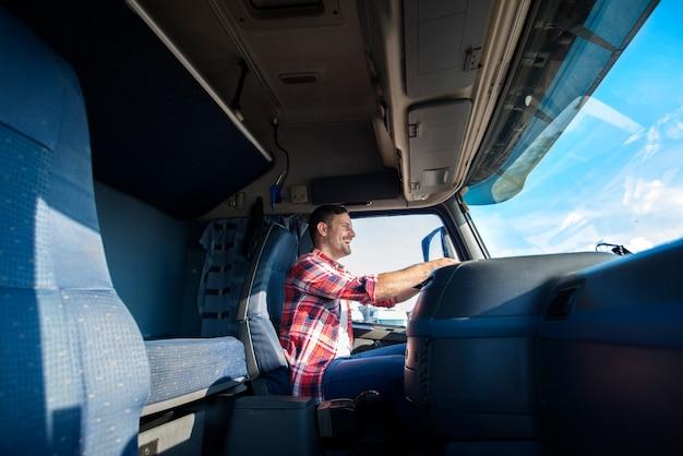 Professioneller trucker mittleren alters, der lkw zum ziel fährt
