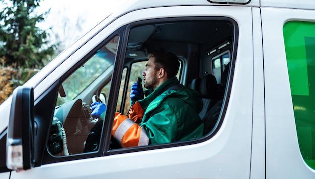 Professioneller und selbstbewusster junger arzt mit krankenwagen