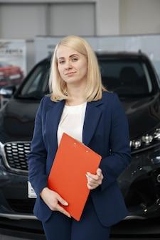 Professioneller verkäufer, der autos im autohaus an käufer verkauft selling