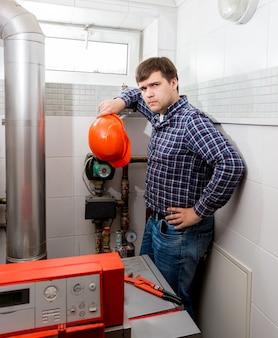 Professioneller verwirrter klempner, der ein kompliziertes heizsystem betrachtet