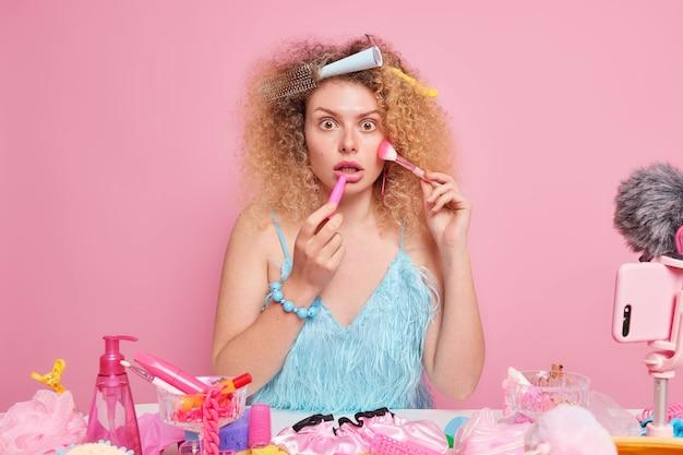 Professioneller videoblogger zeichnet tutorial-video über make-up auf kosmetikpinsel aufträgt lippenstift steht schockiert drinnen