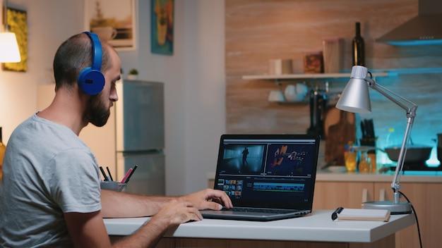 Professioneller videofilmer, der in der videobearbeitungs-app arbeitet und kopfhörer vor dem laptop trägt, der in der heimischen küche sitzt. freiberufler, der um mitternacht audiofilmmontagen auf einem professionellen laptop verarbeitet