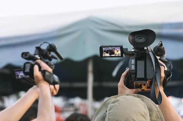Professioneller videokameramann, der bei der veranstaltung mit seiner ausrüstung arbeitet.