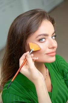 Professioneller visagist, der puder durch pinsel auf wangen der schönen jungen kaukasischen frau im schönheitssalon anwendet
