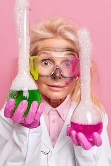 Professioneller weiblicher chemsit hält zwei flaschen mit bunter flüssigkeit zeigt chemische experimente im labor trägt eine schutzbrille weiße robe und gummihandschuhe schmutzig nach unerwarteter explosion