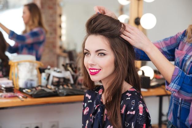Professioneller weiblicher friseur, der einer fröhlichen jungen frau mit langen haaren frisur macht