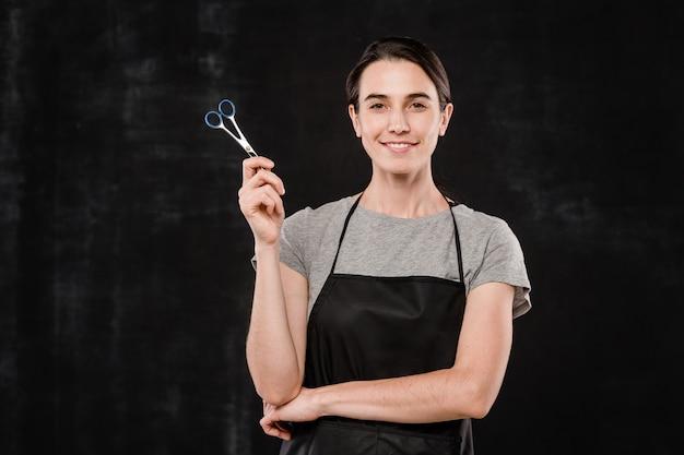 Professioneller weiblicher friseur in der schwarzen schürze, die schere hält, während sie isoliert betrachten
