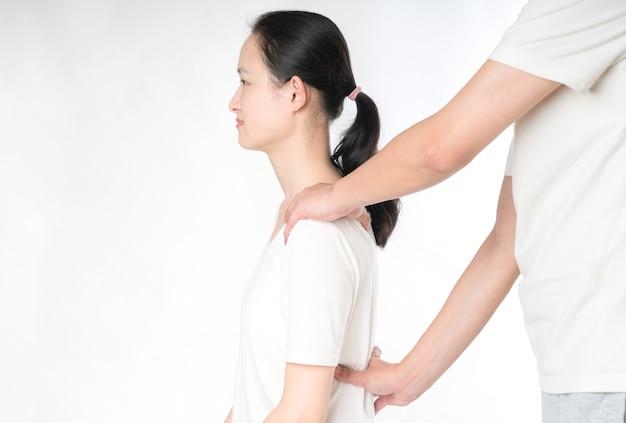 Professioneller weiblicher physiotherapeut, der dem mann im krankenhaus schultermassage gibt
