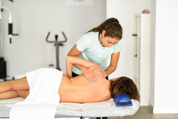 Professioneller weiblicher physiotherapeut, der einer frau schultermassage gibt