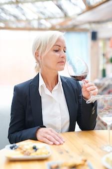 Professioneller weiblicher sommelier, der durch holztisch sitzt, während geruch und geschmack von rotwein im restaurant bewertet