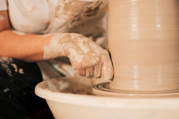 Professioneller weiblicher töpfer, der lehm auf der töpferscheibe glatt macht
