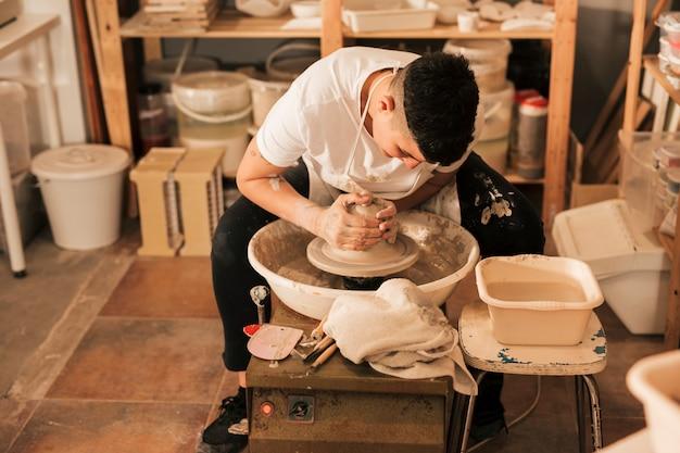 Professioneller weiblicher töpfer, der topf in der tonwarenwerkstatt macht