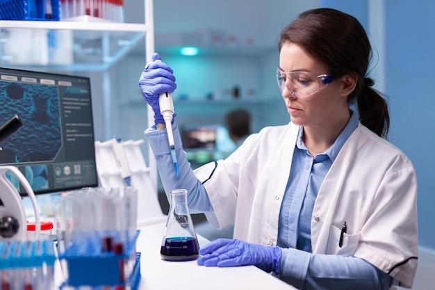Professioneller wissenschaftler, der probe für medizinisches experiment nimmt