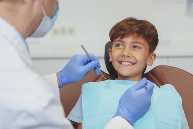 Professioneller zahnarzt, der zähne eines reizenden jungen prüft
