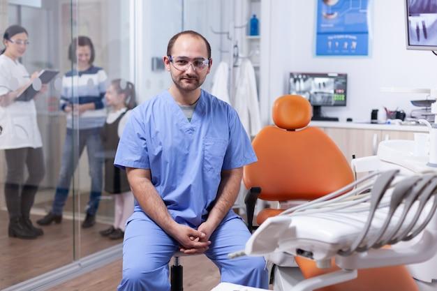 Professioneller zahnarzt mit schutz und patientendiskussion mit kieferorthopäden. brille stomatolog in professioanl zahnklinik lächelnd in uniform mit blick in die kamera.