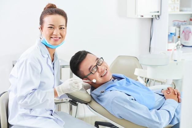 Professioneller zahnarzt und fröhlicher patient