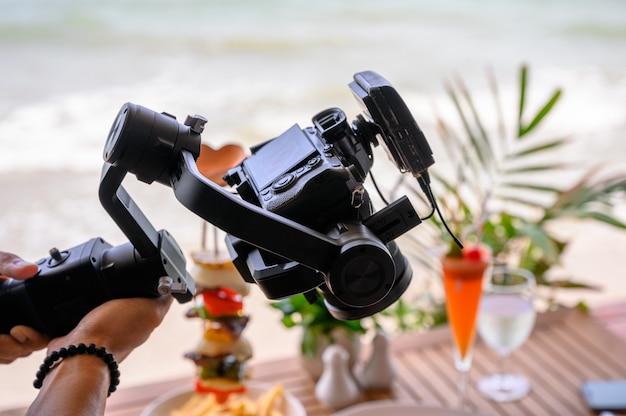 Professionelles arbeiten mit spiegelloser kamera und kabellosem mikrofon am kardanstabilisator
