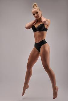 Professionelles athletentraining, seitenansichtfoto in voller länge. isolierte weiße wand. gesundheit und körperpflege, wellness.
