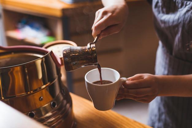Professionelles barista serviert traditionellen türkischen kaffee in der cafeteria