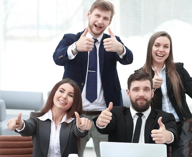 Professionelles business-team zeigt daumen hoch.