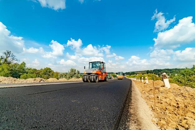 Professionelles equipment legt und richtet im sommer frischen asphalt auf der autobahn aus.