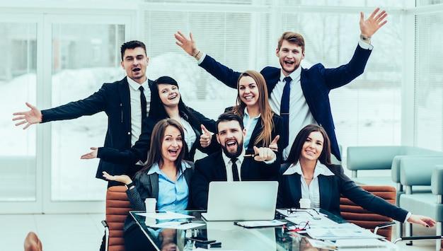Professionelles geschäftsteam freut sich über die errungenschaften der gemeinsamen arbeit. das foto hat einen leeren platz für ihren text