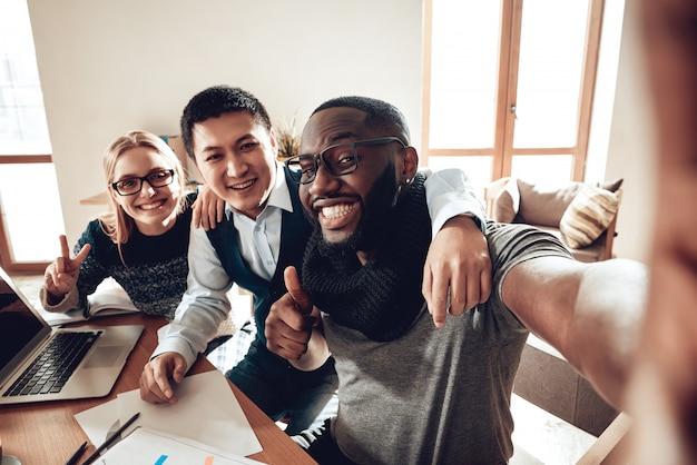 Professionelles glückliches junges team selfie im büro