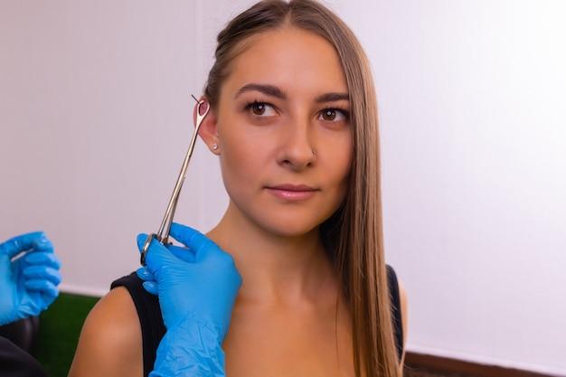 Professionelles halten des juwels des piercings, kurz bevor die kugel geschraubt wird