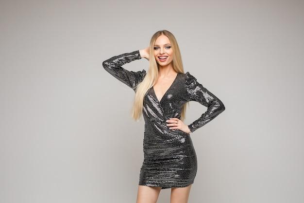 Professionelles kaukasisches weibliches modell mit langen weißen haaren wirft ein kurzes schwarzes kleid auf und lächelt