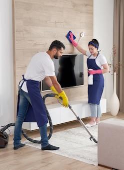 Professionelles reinigungsservice-team reinigt wohnzimmer in moderner wohnung