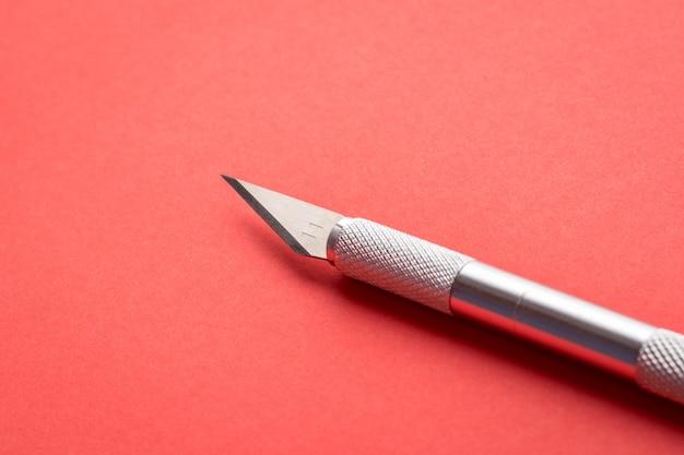 Professionelles skalpell für papierkram auf rotem papier für kunst
