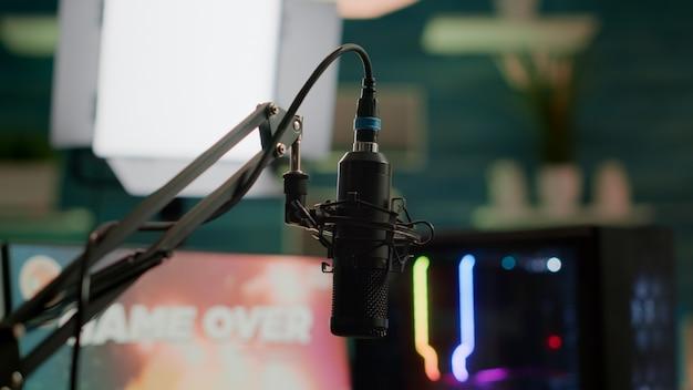 Professionelles streaming-mikrofon im leeren gaming-heimstudio mit neonlicht. das spiel ist vorbei auf dem professionellen rgb-computer und der stream-chat ist für das virtuelle turnier vorbereitet