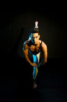 Professionelles tanzen des männlichen ballettausführenden im scheinwerferlicht