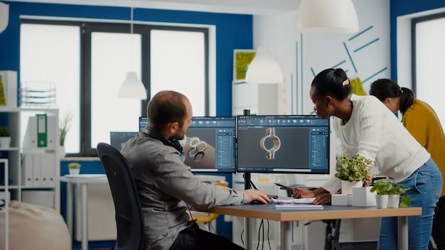 Professionelles team von ingenieuren aus der schwerindustrie, die an einem computer mit zwei monitoren mit cad-software arbeiten.