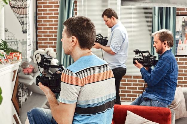 Professionelles team von kameraleuten mit einem regisseur, der werbeanzeigen filmt