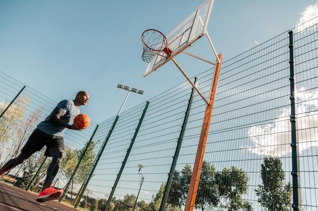 Professionelles training. hübscher afroamerikanischer mann, der einen ball hält, während er ein training hat