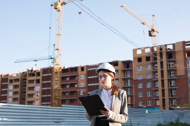Professionelles weibliches architekturschreiben auf klemmbrett an der baustelle