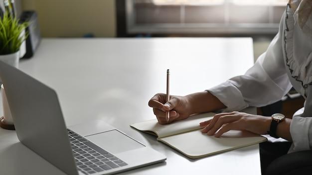 Professionelles weibliches schreiben auf notizbuchpapier, geerntete schussfrau, die an tabelle arbeitet.