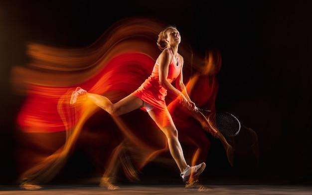 Professionelles weibliches tennisspielertraining lokalisiert auf schwarzem studiahintergrund in gemischtem licht. frau im sportanzug üben.