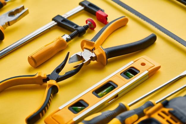 Professionelles werkstattinstrument. tischlerwerkzeuge, baumaschinenausrüstung, schraubendreher und pfähle, bügelsäge und wasserwaage