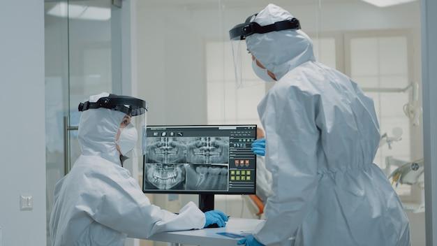 Professionelles zahnärztliches personal mit ppe-anzug, das zähne röntgen betrachtet