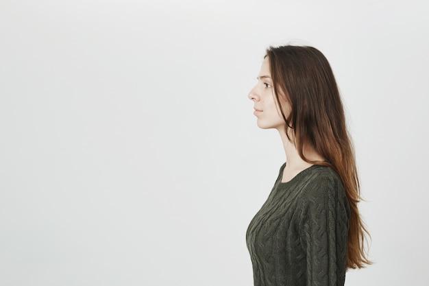 Profil der attraktiven jungen frau im grünen pullover mit langen haaren