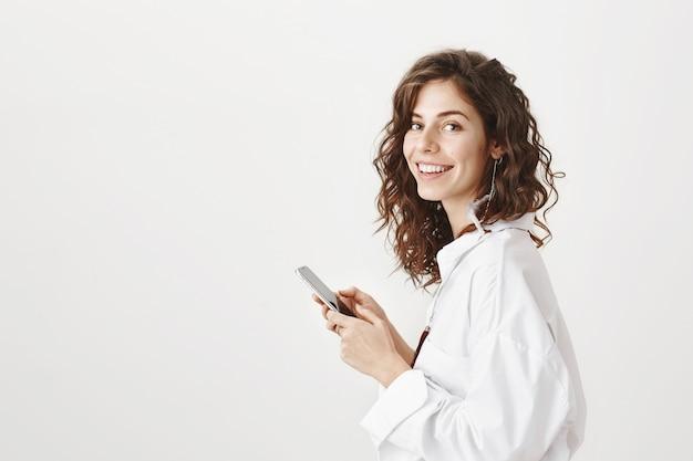 Profil der attraktiven kaukasischen frau unter verwendung des smartphones