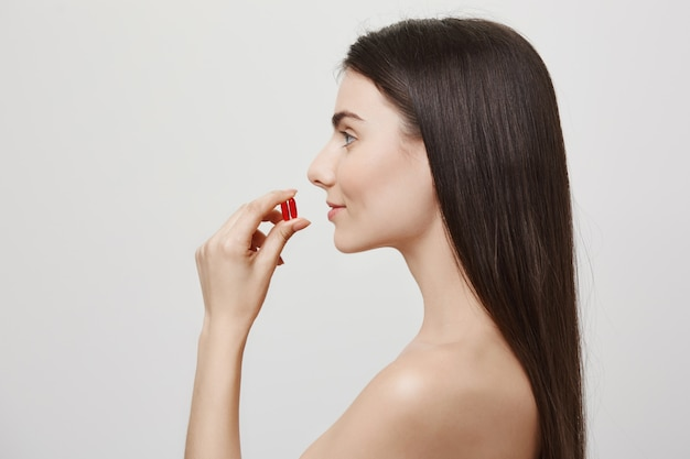 Profil der attraktiven nackten frau, die vitamine nimmt