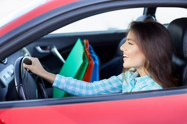 Profil der frau, die im roten auto sitzt, glücklicher fahrer. frau, die nach vorne schaut und lächelt. kopf und schultern der glücklichen frau, die das ruder hält und vom einkaufen zurückkommt