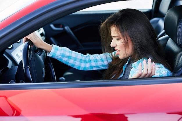 Profil der frau, die rotes auto, stress während der fahrt fährt. angespannte frau, die das ruder hält, staus. kopf und schultern der brünetten frau im auto