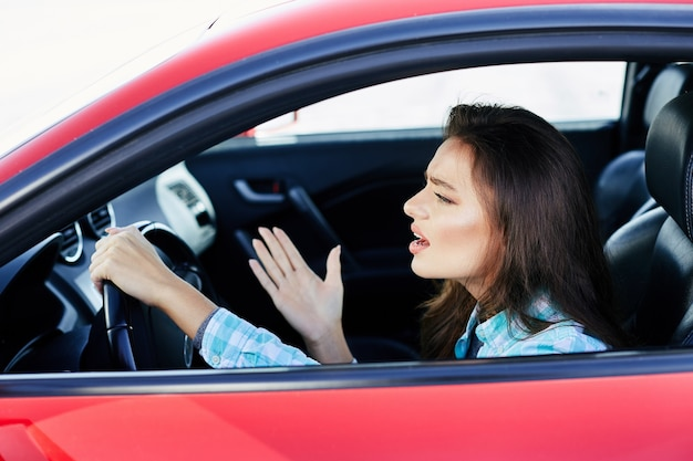 Profil der gestressten frau, die rotes auto fährt, stress während der fahrt. frau, die nervös nach vorne schaut, staus. kopf und schultern der brünetten frau im auto