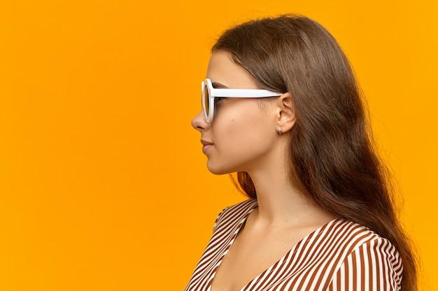 Profil der glamourösen attraktiven jungen frau mit losen haaren, die sommerkleid tragen