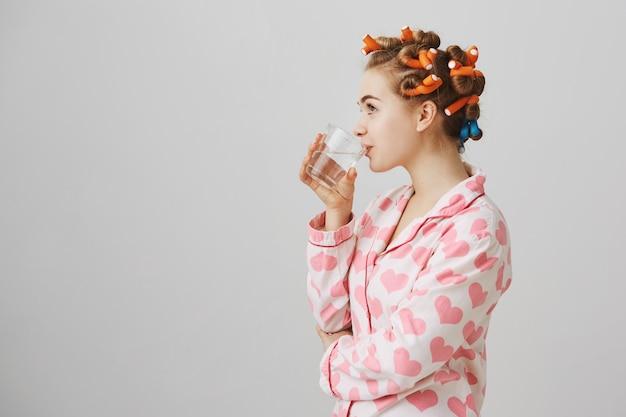 Profil der jungen frau mit den lockenwicklern, die wasser im schlafanzug trinken